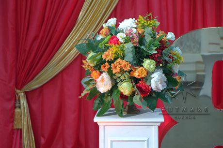 Золотая ваза с цветами в украшении зоны для фотографирования