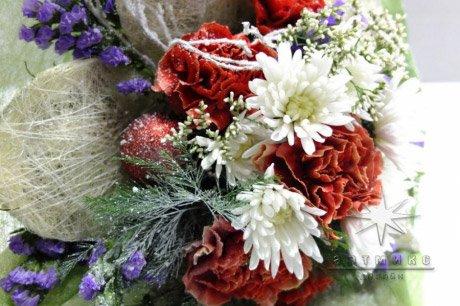 Подарочный букет на Новый год состоит из веточек хвойных деревьев, гвоздики, хризантемы и елочных игрушек