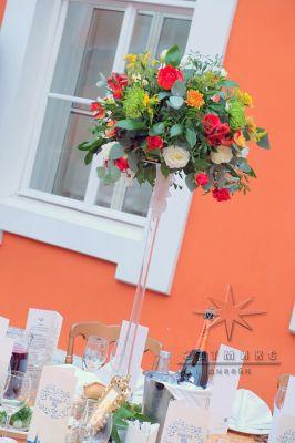 Высокие стеклянные вазы с цветами на столах гостей