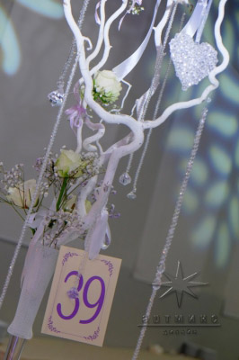 Высокие прозрачные вазы изящной формы наполнены белые веточки и на них красуются прозрачные кристаллики в виде капель