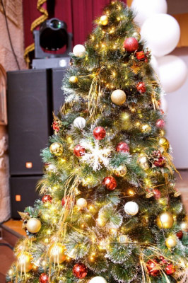 Яркая новогодняя елка с подарками оформлена у сцены на корпоративном празднике