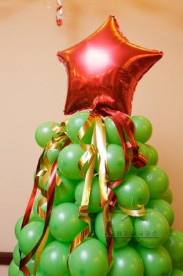 Новогодняя зеленая елочка из воздушных шаров представлена в фойе банкетного зала ресторана