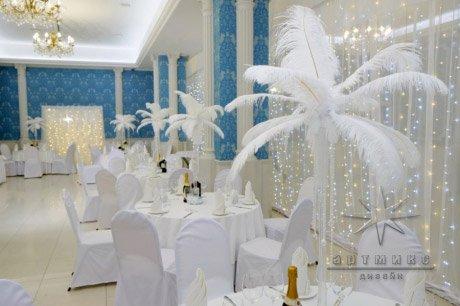 Белоснежные перья на столах гостей в оформление банкетного зала на новогоднее мероприятие