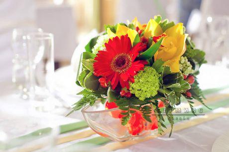 Красные герберы и желтые орхидеи в оформлении праздничного стола
