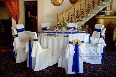 Оформление стульев широкой лентой синего цвета и бант из золотой парчи на юбилей