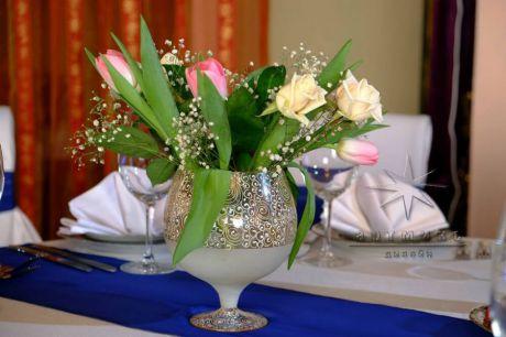 На синем напероне с живыми цветами в вазоне для украшения столов гостей на праздничном торжестве