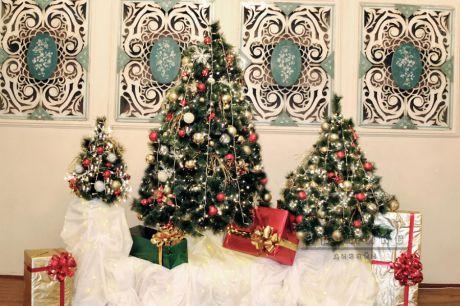 Оформление сцены елочками и подарками в банкетном зале для празднования нового года