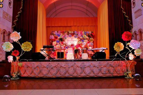 На заднике сцены панно из цветов с монограммой