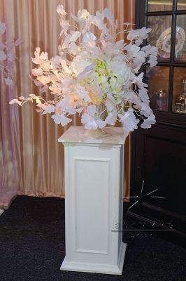 Белые ветки Гинкго билоба в вазе на высокой тумбе