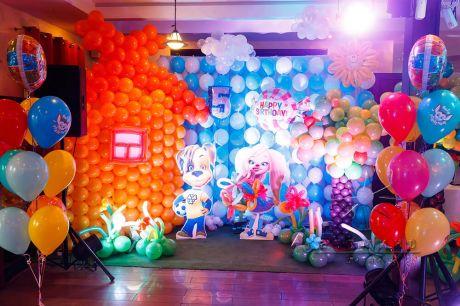 Стена из шаров для фотосессии выполнена в стиле цветочной поляны, а в середине симпатичные мультперсонажи