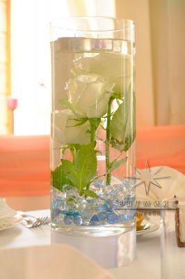 Одиночные вертикально стоящие белые розы в прозрачной вазе