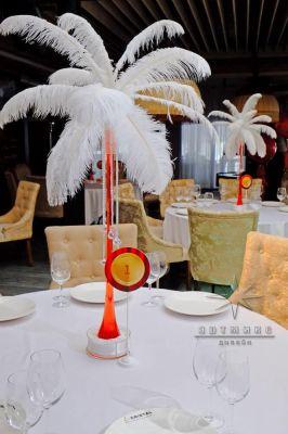 Декоративные перья в вазах на столе гостей