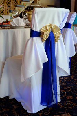 Стулья для гостей украшены тканевыми лентами насыщенного синего цвета с золотыми бантами