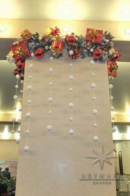 Украшение из веток шаров и подарков колоны в банкетном зале