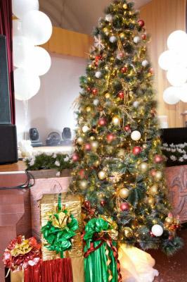Оформление на рождество - елки, яркими игрушками, мишурой, гирляндами у сцены в ресторане