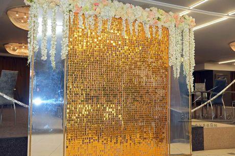 Фон из золотых пайеток, зеркалами с дух сторон и цветочной гирляндой