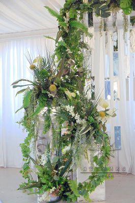 Зеркальные колонны оформлены в экзотическом стиле с добавлением цветов и листьев