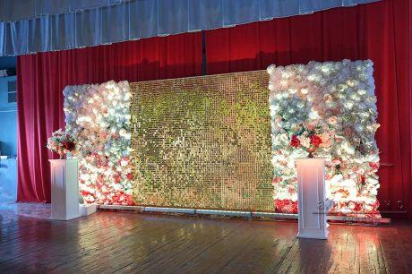 Задник сцены оформлен фоном из золотых пайеток