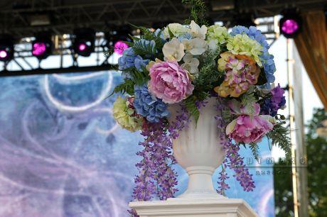 Декоративные белые тумбы с цветами на сцене