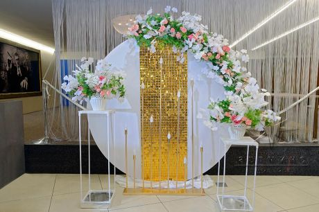 Круглая фотозона с золотыми пайетками и цветочными композициями