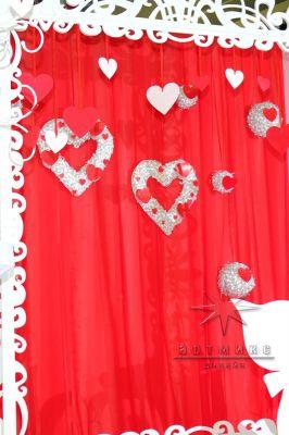 Фон фотозоны оформлен сердцами, в стиле праздника