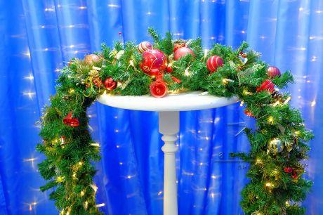 Еловая гирлянда, украшенная новогодними шарами, шишками, бантиками и маленькими лампочками