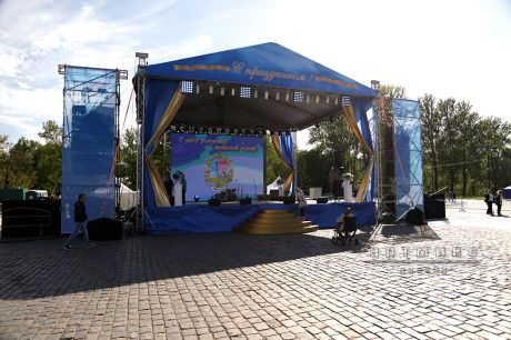 Декоративное оформление баннерами, тканями и цветами уличной сцены праздника День Города Кронштадта