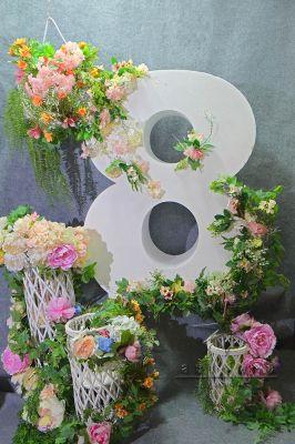 Цифра 8 окружена плетёными, белыми фонарями с цветами