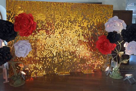 Фотозона из золотых, движущихся пайеток с чёрно-красно-белыми цветами из дизайнерского картона