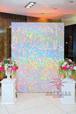 Фотозона из перламутровых пайеток с декоративными напольными колоннами и яркие цветочными композициями