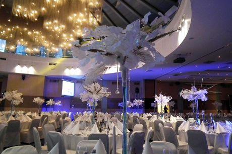 Новогоднее оформление зала высокими вазами с композициями из перьев и веточками Гинкго