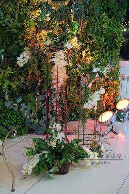 На зелёном ковре установлена декорация деревянные  корзинки с полевой травой и цветами