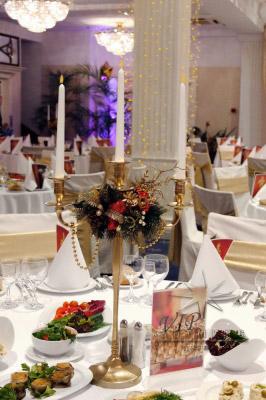 В центральной части праздничного стола расположен новогодний канделябр, оформленный веточками елки, шишками и новогодними игрушками