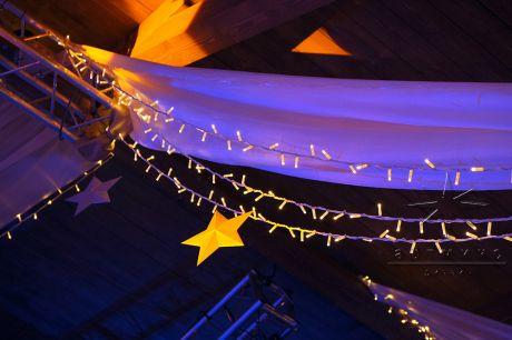 Праздничное оформление потолка звёздами, гирляндой и воздушным текстилем