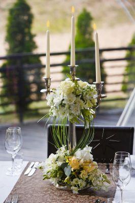 Канделябр, оформлен цветочной композицией станет необычным украшением зала