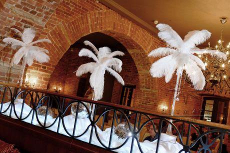 Украшение зала на юбилей в стиле Кабаре, где перья на столах играют неотъемлемую часть на празднике
